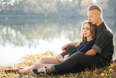 Date in park. Young male and female sitting near water hugging having good time Stock Photo