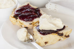 Date Scone with Jam and Cream. Dates scone, split and spread with jam and cream, on a plate Royalty Free Stock Photography