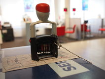 Date stamp chain tied to a desk. Standing on a stamped paper in an office surroundings royalty free stock photography
