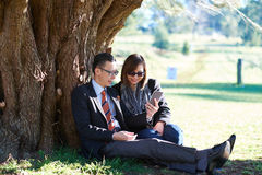 Couple sitting under a tree on a sunny day. Looking at phone royalty free stock image