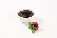 Date syrup with dates. Bowl of date syrup with dates on white background Royalty Free Stock Photography