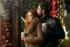 Date on Valentine`s Day. Date for Valentine`s Day. Guy hugs and kisses his girlfriend. They drink warming drink from paper cups. Tenderness and care. Festive royalty free stock photo