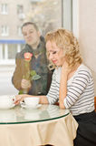 Date. Young woman waits a boyfriend at small cafe Stock Photo