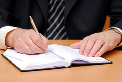 Datebook. Businessman write down to the datebook Royalty Free Stock Image