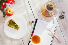 Datebook, flower, cup of tea, chicken pie, apple, glass teapot and watch on wooden table. Datebook, pencil, cup of tea, chicken pie, apple, glass teapot and Royalty Free Stock Photos
