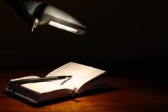 Datebook Under Lamp. Fountain pen on open datebook under luminous table lamp Royalty Free Stock Photography