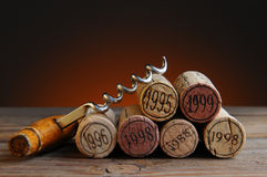 Dated Wine Corks and Corkscrew. Closeup of a group of wine corks and a corkscrew on a rustic wood table and a light to dark warm background Royalty Free Stock Photo