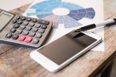 Daten, die mit Taschenrechnerhandy und -stift auf hölzernem ta analysieren Stockfotos