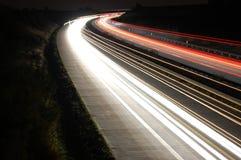 Datenbahn nachts mit Verkehr stockbild
