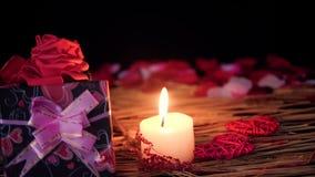 Dater la décoration de Saint Valentin avec des boîte-cadeau, bougie brûlant et pétales banque de vidéos