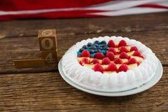 Datera kvarter och fruktkaka på trätabellen med 4th det juli temat Arkivfoton