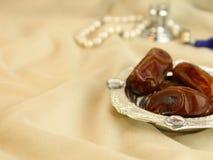 Dates Arabes avec le masbah de perles de perle et le bokeh de parfum photographie stock libre de droits