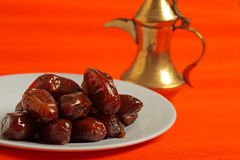Dates and arabic tea pot. Dates and golden arabic teapot in the background Royalty Free Stock Photography
