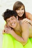 Dates on the beach. Portrait of teenage girl and her boyfriend lying on mattress and sunbathing Stock Photo