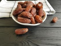 Dates on a black wooden towel food healthy ingredient heap nutrition. Dates on a black wooden towel heap dessert healthy eastern nutrition ingredient food Stock Photography