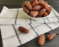 Dates on a black wooden towel food  snack healthy ingredient heap nutrition. Dates on a black wooden towel heap dessert healthy eastern nutrition ingredient food Royalty Free Stock Photos
