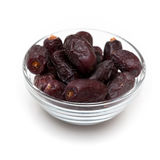 Dates in a bowl. Close up shot of date fruits in a glass bowl isolated on white Stock Photo