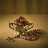 Dates bowl and rosary Royalty Free Stock Images