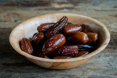 Dates in a bowl. On a wooden table Royalty Free Stock Photos