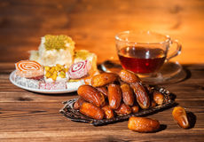 Dates, candy and cup of tea, concept of muslim feast holy month Royalty Free Stock Images
