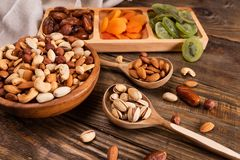 Dates, dried apricots and kiwis in a Compartmental dish and assortment of nuts in wooden bowl on a dark wooden table. Copy space stock photos