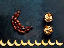 Dates fruit arranged in shape of crescent moon on vintage rusty metal background. stock photos