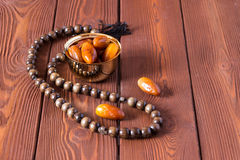 Dates fruit and rosary still life, on a brown wooden background royalty free stock photo