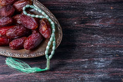 Dates fruit and rosary still life, on a dark wooden background. ramadan food concept. royalty free stock photo