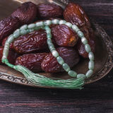Dates fruit and rosary still life, on a dark wooden background. ramadan food concept. royalty free stock images