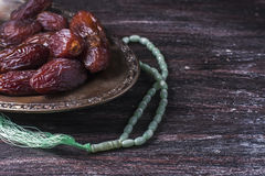 Dates fruit and rosary still life, on a dark wooden background. ramadan food concept. stock photos