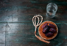 Dates fruit and rosary still life, on a dark wooden background. stock photos