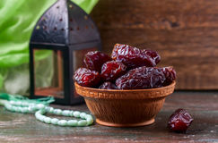 Dates fruit and rosary still life, on a dark wooden background. royalty free stock image