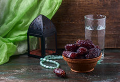 Dates fruit and rosary still life, on a dark wooden background. royalty free stock photography