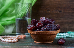 Dates fruit and rosary still life, on a dark wooden background. Stock Images