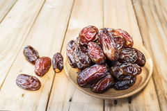Dates fruit in a wooden bowl closeup on wooden Stock Photo