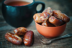 Dates fruits in bowl and tea cup on background. Stock Photo