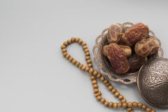 Dates fruits on a copper bowl with rosary beads on a gray background stock photos