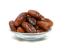 Dates in a glass bowl on a white background Royalty Free Stock Images