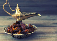 Dates and golden arabian lamp on wooden background. Oriental foo Royalty Free Stock Photos