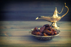 Dates in golden bowl and arabian Aladdin lamp. Vintage style Royalty Free Stock Images