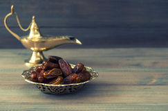 Dates in golden bowl and arabian lamp. Retro style toned picture stock photo