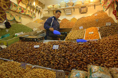Man selling dates and nuts in market. A date and nut stall in the Souk market in Marrakesh, Morocco Royalty Free Stock Photo