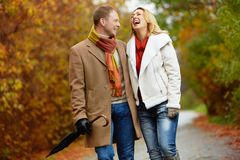 Dates in park. Portrait of ecstatic couple during walk in autumnal park Stock Photos