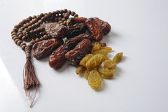 Dates,raisin and rosary  on white background Stock Images