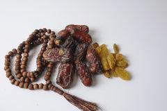 Dates,raisin and rosary  on white background Royalty Free Stock Image