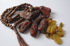 Dates,raisin and rosary  on white background Royalty Free Stock Photos