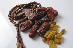 Dates,raisin and rosary  on white. Islamic concept Stock Image
