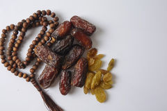 Dates,raisin and rosary  on white. Islamic concept Royalty Free Stock Photography