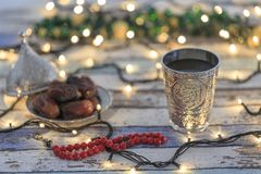 Dates, rosary, and water cup with Allah text in arabic. In lights background stock images