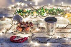 Dates, rosary, and water cup with Allah writing in arabic. In lights background royalty free stock photo